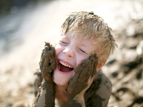 A cute little boy child is laughing as he plays outside in the mud and rubs dirt on his face with his hands.