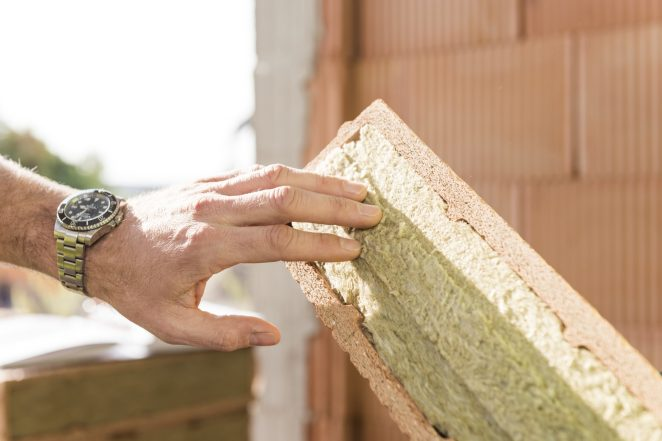 Hand touching mineral wool of internal insulation filled clay block